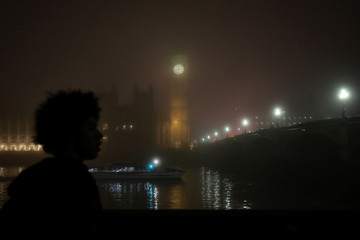 A man views the Big Ben clock tower during a foggy evening in London