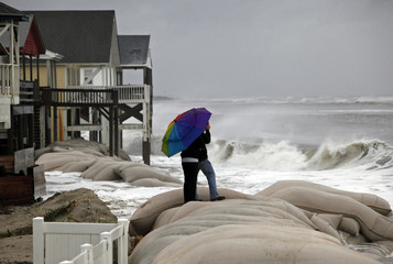 Cage Deal, with the help of his mother Christy, get video footage as the winds of Hurricane Sandy pounds waves onto the east side of Ocean Isle Beach,