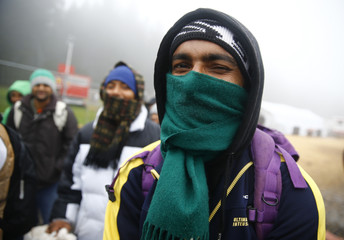 Migrants wrap-up against the cold weather at temporary registration centre in the village of Schwarzenborn