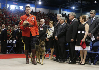 A Royal Canadian Mounted Police officer arrives with the hat and dog of K-9 officer David Ross, one of three officers killed last week, during a regimental funeral in Moncton
