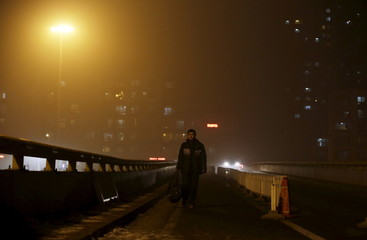 A man walks on an overpass amid heavy smog in Beijing