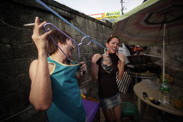 Entertainers Clifford and Regina joke in the yard outside their room in Cebu