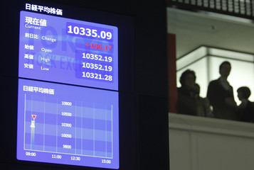 Visitors are seen next to an electronic board showing stock prices at the Tokyo Stock Exchange after the New Year opening ceremony in Toky