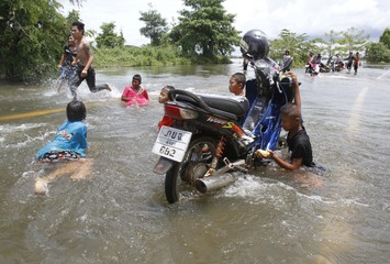 Children wash a motorcycle in a flooded road in Phichit province