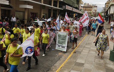 Domestic workers march through a street calling for higher wages and better opportunities on Domestic Workers' Day in Asuncion