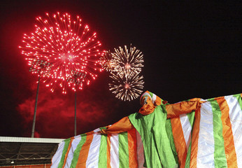 A man dressed in a costume bearing the colors of the Ivory Coast flag stands as fireworks are seen during celebrations for Ivory Coast's 50th Independence Day in Abidjan