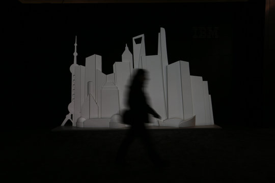 A person walks past an illuminated skyline at the booth of IBM at the CeBIT trade fair in Hanover