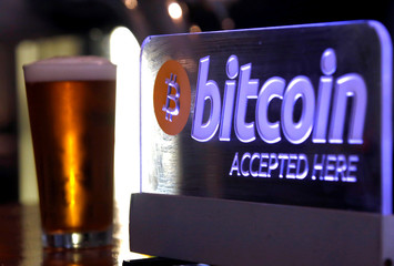 A beer sits next to a Bitcoin sign on display at a bar in central Sydney, Australia