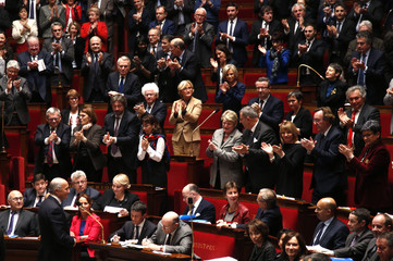 French Foreign Affair Minister Laurent Fabius (bottom,L) reacts as deputies applaud during the questions to the government session at the National Assembly in Paris