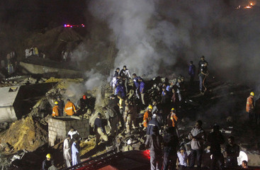 Rescue workers stand near the site of an airplane which crashed in Karachi