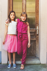 Outdoor fashion portrait of two fashion preteen girls