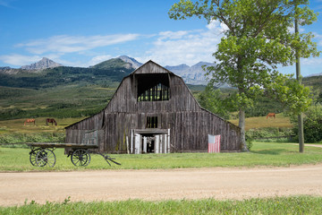 horizontal image of an old run down barn with an American flag hanging from it and a wooden hauling wagon sitting in the yard with beautiful mountains in the background with horses grazing in pasture.