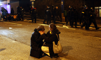 A girl takes care of her injured friend as Slovak police disperse people during an election protest in Bratislava