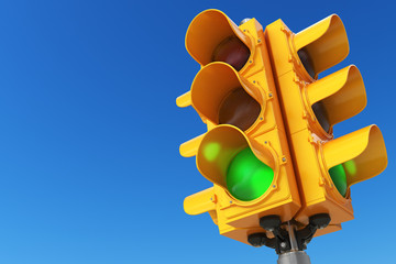 Traffic light with green color on blue sky background.