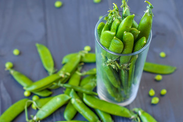 Young green peas in a glass on a wooden table.