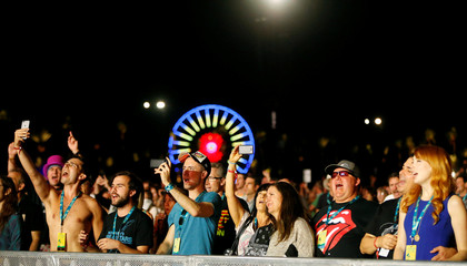 Concertgoers sing along during a performance by musician Paul McCartney at Desert Trip music festival at Empire Polo Club in Indio