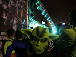 A woman wears a Yoda mask on the back of her head as she takes pictures of a show before the Star Wars Run race ahead of Star Wars Day in Buenos Aires