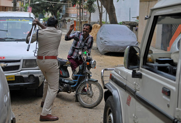 Police stop a man during a curfew in Bengaluru, following violent protests after India's Supreme Court ordered Karnataka state to release water from the Cauvery river to the neighbouring state of Tamil Nadu