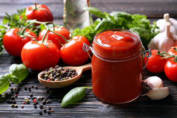 Fototapeta Composition of ketchup in jar and ingredients on wooden background, closeup obraz