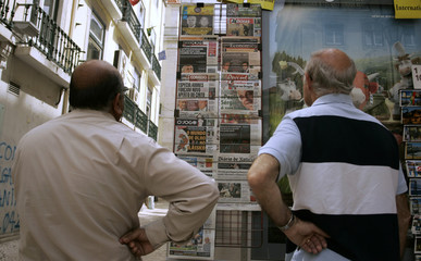 People read the newspapers at a kiosk in downtown Lisbon