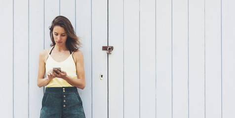 Fotomurales - Portrait young women using smart phone isolated on background vintage wooden boards wall background mock up, pretty hipster female hands text message holding mobile gadget, blurred summer backdrop