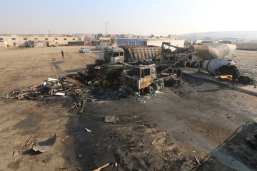 A general view shows damaged trucks after what activists said were air strikes carried out by the Russian air force, on a parking garage for cargo trucks in al-Dana town