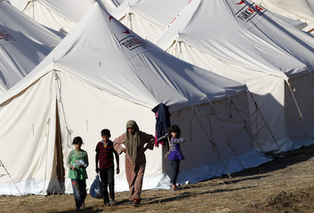 Syrian refugees walk at a refugee camp in the Turkish border town of Yayladagi in Hatay province