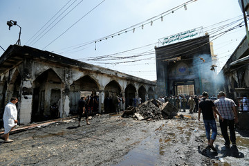 People gather at site of a suicide attack at the entrance of the Shi'ite Mausoleum of Sayid Mohammed bin Ali al-Hadi in Balad, north of Baghdad