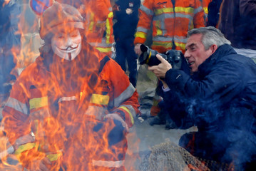 A photographer takes pictures near a Belgian firefighter wearing a Guy Fawkes mask while standing behind a fire the firefighters started as a protest to demand better working conditions, in central Brussels