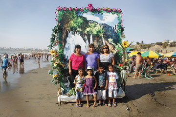 People pose in a photography booth at Agua Dulce beach in Lima's district of Chorrillos
