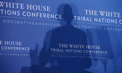 U.S. President Obama casts a shadow on the background as he speaks at the 2013 White House Tribal Nations Conference at the Department of the Interior in Washington