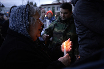 A woman sings Amazing Grace at a candlelight vigil for mudslide victims in Arlington