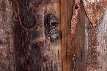 agricultural tools hanging on brown wooden wall