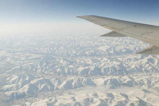 The Brooks mountain range spreads out to the horizon below the wing of an airplane in Alaska