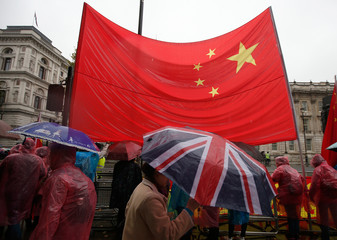 A police officer takes a picture for supporters of China's President Xi Jinping outside Downing Street in central London, Britain