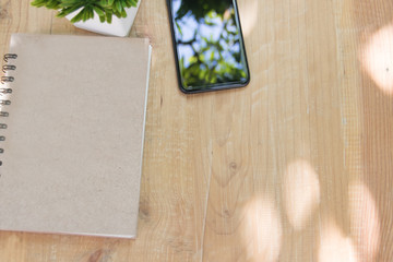 Book and smart phone with blank screen on wooden table.top view angle
