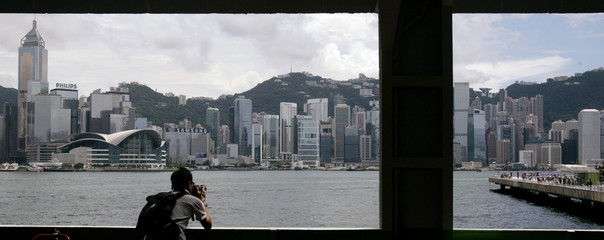 Man takes pictures of the Victoria Harbour during the Hong Kong International Dragon Boat Races in Hong Kong