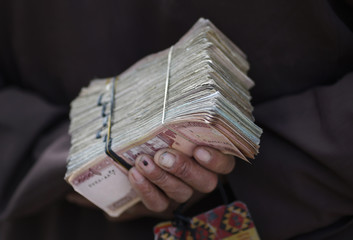 Money changer holds a stack of Afghan currency on a street in central Kabul