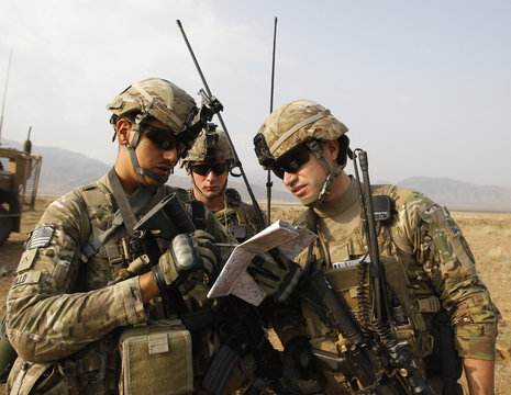 """U.S. soldiers from Alpha Co, 2nd Battalion 35th Infantry, Task Force """"Cacti"""" read their grid on a map during a joint U.S.-Afghan military patrol in Serkey valley in Kunar"""