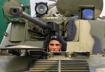 A Ukrainian soldier mans an APC at a military camp the Ukrainian Army forces have set up close to the Russian border in east Ukraine