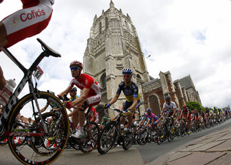 The pack of riders cycles past the church of Aire-sur-la-Lys during the third stage of the 99th Tour de France cycling race between Orchies and Boulogne sur mer
