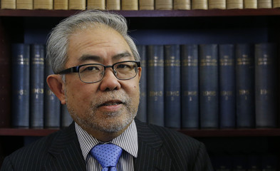 Solicitor Wah-Piow Tan poses in his office in west London