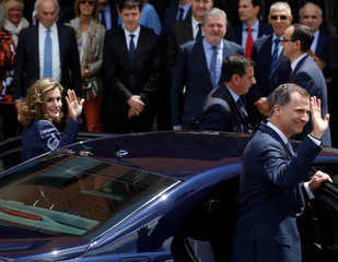 Spain's Queen Letizia and King Felipe wave as they take their car after opening an exhibition of late Dutch artist El Bosco at El Prado museum in Madrid