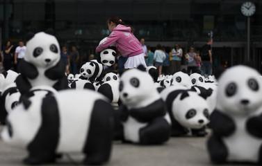Girl plays with panda bear sculpture in Berlin