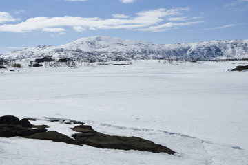 View over a frozen lake with snowmobile tracks and a Sami village and a snowy mountain
