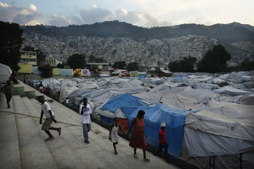 People walk near makeshift shelters in Port-au-Prince