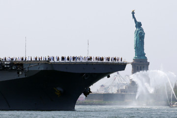 The wasp-class amphibious assault ship USS Bataan passes the Statue of Liberty as it arrives in New York Harbor to mark the beginning of Fleet Week in New York