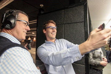 John Nelson takes a selfie with U.S. Republican presidential candidate Rick Santorum and the gun he used for target practice at the Central Iowa Impact shooting range in Boone, Iowa