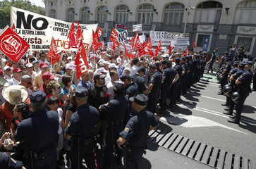 Demonstrators shout slogans as they stand in front of the police during a protest against the labour reform of the Spanish government in Madrid