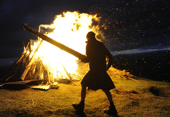 Richard Teall feeds the beacon on top of Ben y Brackie that was lit for the Diamond Jubilee celebrations of Britain's Queen Elizabeth, in Pitlochry, Scotland